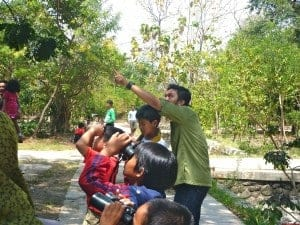 Kids are watching birds with binoculars lent by the instructor. They learnt how to get the lenses focus too.