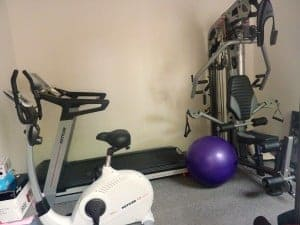 As you can see, the gym room is very crowded with a machine, a treadmill, an exercise ball and an exercise bike.